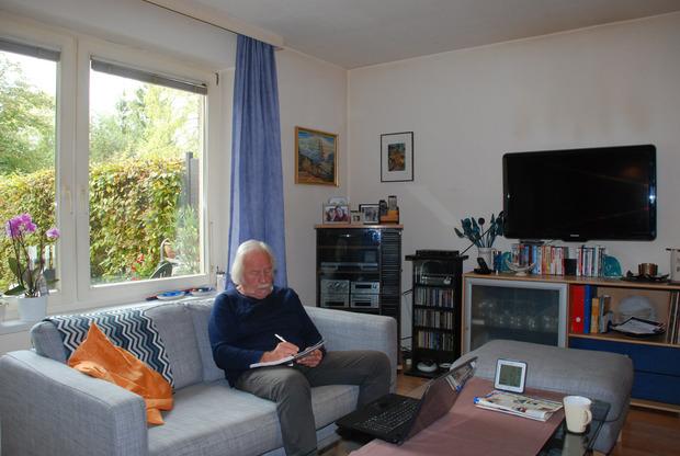 """Viktor Haid eim Verfassen des nächsten """"Herr Reindl""""-Beitrags im Wohnzimmer seines Hauses - mit Füllfeder trotz Laptop."""