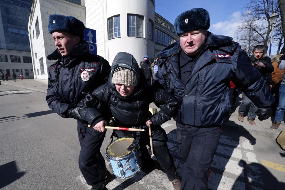 Russische Polizisten führen eine Aktivistin ab.