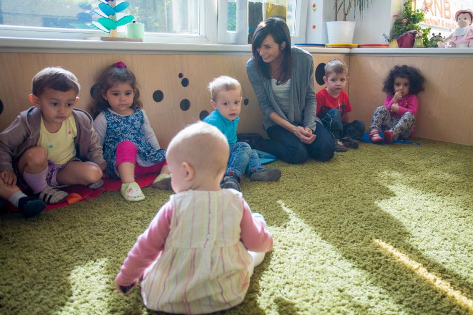 Krippenleiterin Andrea Weiskopf und ihre Schützlinge begrüßen Baby Clara in der Innsbrucker Kinderkrippe emil.