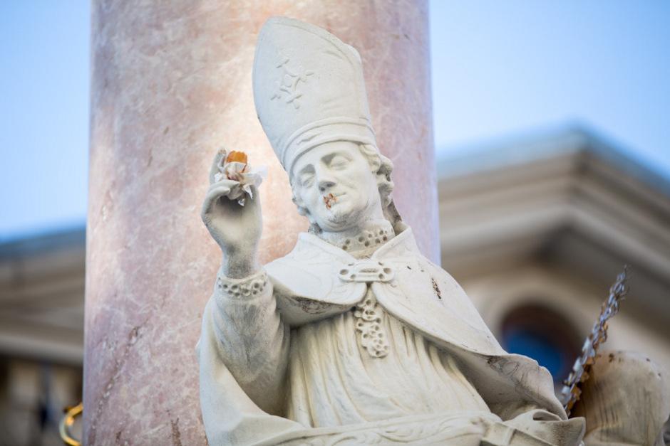Der Bischofsstab ist wieder einmal weg, stattdessen hält der heilige Vigilius ein Hotdog in der Hand, sein Mund ist mit Ketchup beschmiert.
