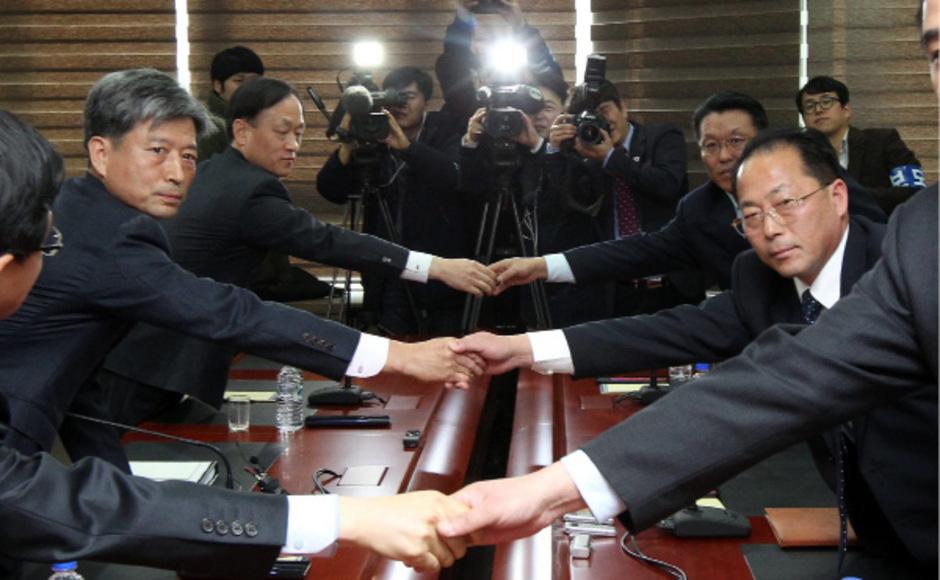 Die Verhandler reichen sich vor Beginn der Gespräche die Hände.