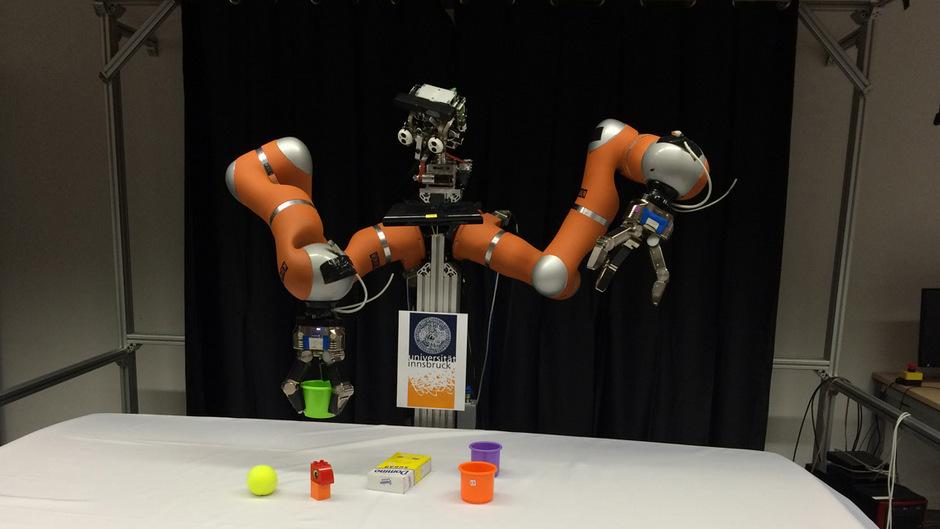 """Der Roboter greift nach einem grünen Becher. Wie der Gegenstand reagiert, """"sieht"""" er mittels Kamera und merkt sich das. Die Maschine bekam übrigens den Namen """"Robin"""" verpasst – für Roboter aus Innsbruck."""
