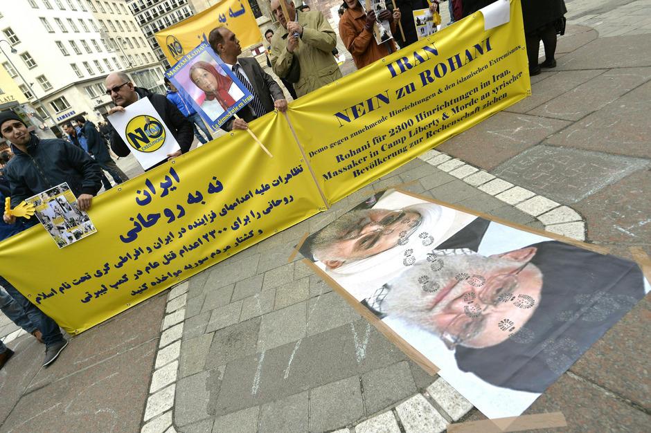 Der iranische Präsident stößt aber auch auf Kritik, wie hier bei einer Demo von Gegnern in Wien.