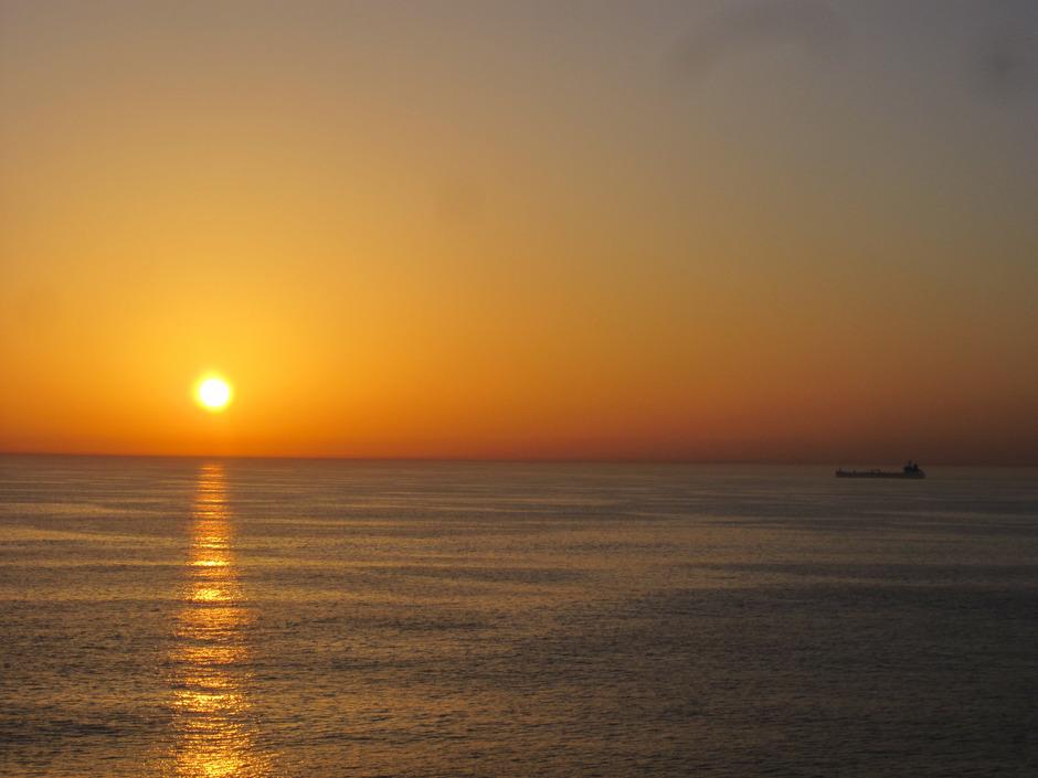 Der Horizont ist das Ziel. Frachtschiff auf der Fahrt über ein spiegelglattes Meer.
