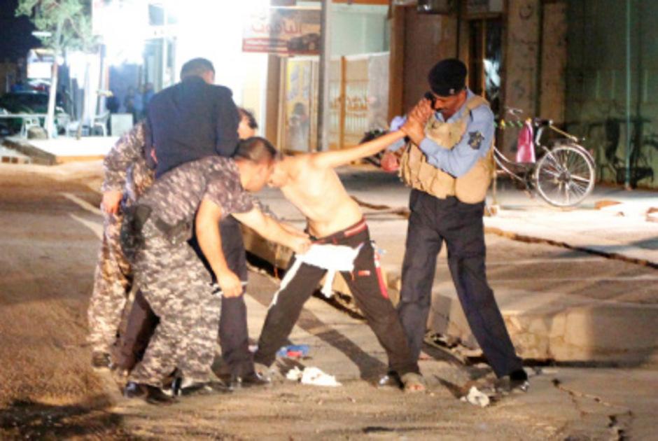 Polizisten halten den Jungen fest. Um die Hüfte trägt er einen Sprengstoffgürtel, den zwei weitere Männer entfernen.