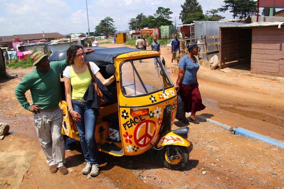 Lungi (l.) führt eine Touristin durch Soweto. Mit dem Tuk-Tuk geht es über die Schlaglochpisten.