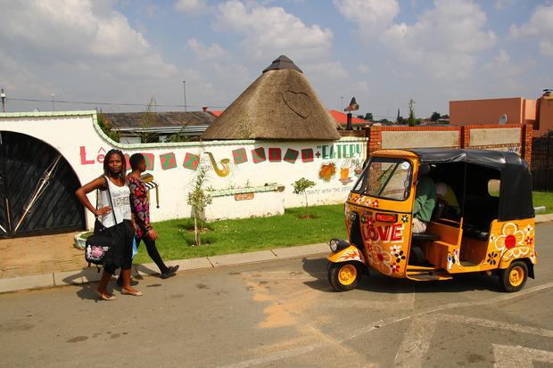 Das Tuk-Tuk fährt durch die besseren Gegenden Sowetos, mit geteerten Straßen.