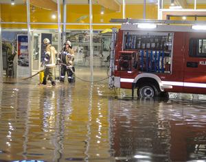 Samstag gegen 22 Uhr, Ortsteil Graf bei Grins: Feuerwehrmänner pumpen Wasser im Eingangsbereich eines Kfz-Händlers ab.