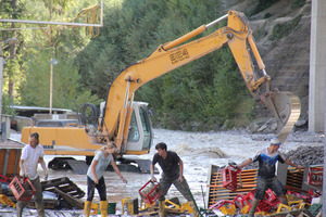 Bei den Aufräumarbeiten im Gewerbegebiet Grins/Graf ist vor allem Körper-Einsatz gefragt. Der Bagger räumt das Flussbett der Sanna.