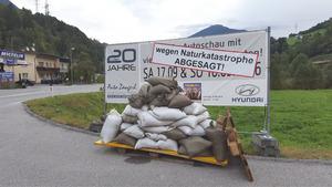 Sandsäcke und ein Info-Plakat vor dem Autohaus Zangerl.