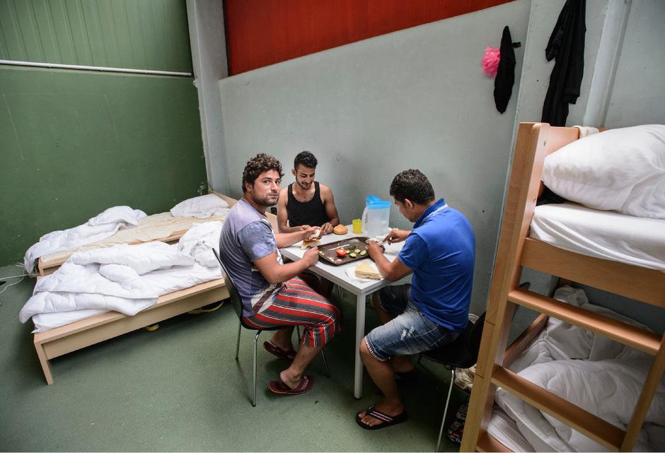 Männer beim Essen im Camp für Asylwerber in der ehemaligen Tennishalle Paschberg in Innsbruck.