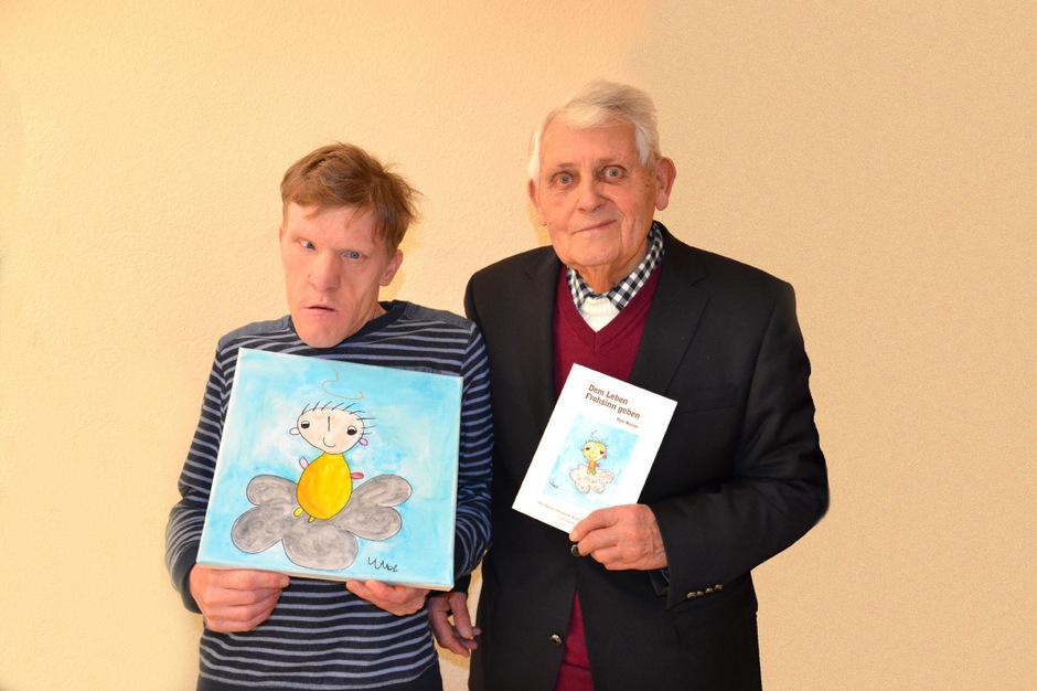 Pepi Wurzer (rechts) mit seinem Buch, in das er erneut viel Witz packte. Von Michael Bacher, der in der Lebenshilfe Osttirol betreut wird, stammt das Titelbild. Das Original wurde dem Autor als Geschenk überreicht.