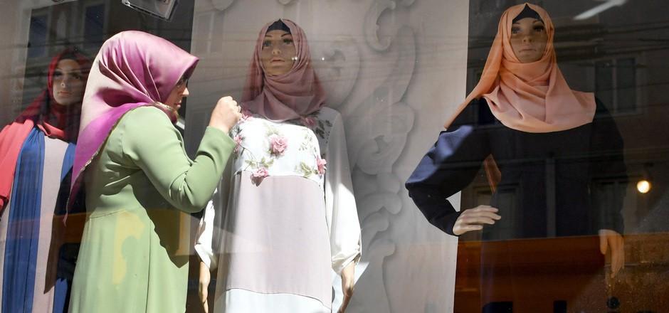 Eine Frau dekoriert die Auslage eines Geschäftes, das Mode für Musliminnen verkauft. 2016 kam es zu Beschmierungen ähnlicher Shops.