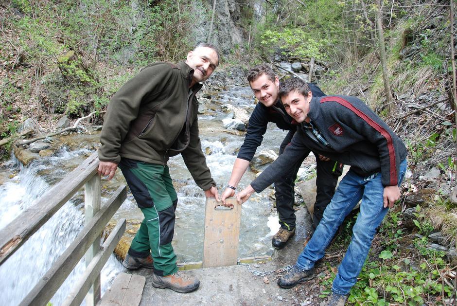 Der Fraunsbach bei Ried im Oberinntal liefert das Lebenselixier für Felder mit 22 Hektar Gesamtfläche. Andreas, Lukas und Mathias Schöpf (v.l.) öffnen das Fallenbrett, um das Wasser in die Waale zu leiten.