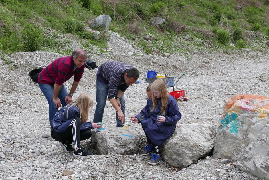 Die Lehrer Gregorius und Anastasios aus Athen bemalen mit Kindern Steine im Flussbett.