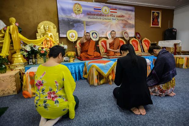 Zwei Mönche segnen die Mitglieder.