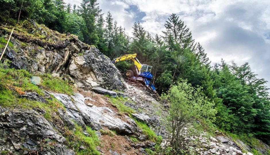 Nach dem Felssturz auf der Pinswanger Straße dauern die Sicherungsarbeiten an. Derzeit trägt ein Schreitbagger den instabilen Felskopf ab.