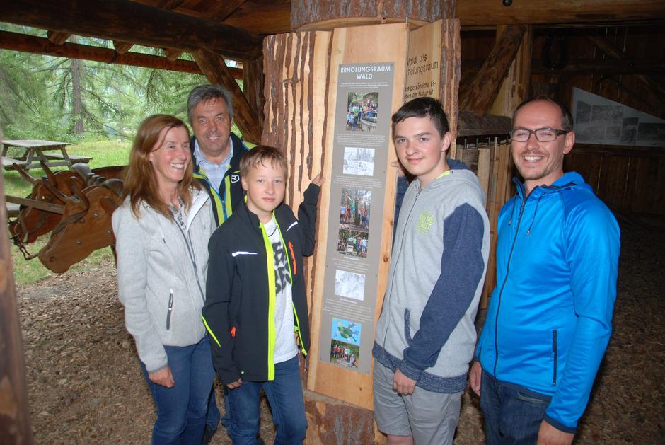 """Biologielehrerin Heidi Padöller, BM Rupert Schuchter, die Schüler Jonas und Kevin sowie Vize-BM Peter Wille (v.l.) hängen die neu gestaltete Seite zum Thema """"Wald als Erholungsraum"""" in das Pfundser Baumbuch ein."""
