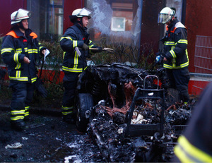 Feuerwehrleute begutachten die Überreste eines ausgebrannten Autos.