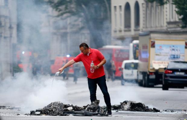 Ein Mann kippt Wasser auf Müll, den Demonstranten in der Nacht in Brand gesetzt haben.