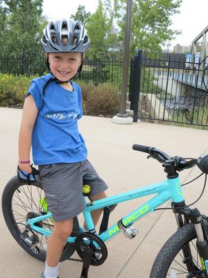 Ben ist stolz auf sein eigenes Rad und den neuen Helm.