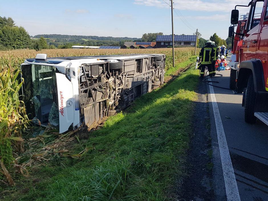 Aus noch ungeklärter Ursache war der voll besetzte Bus von der Landstraße abgekommen und auf die Seite gekippt.