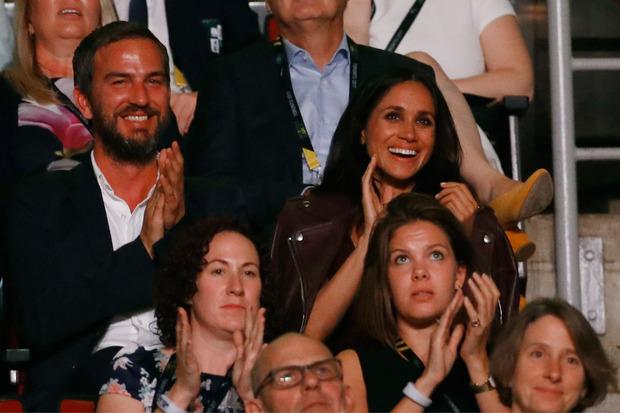 Während Prinz Harry auf der Bühne stand, lachte und klatschte seine Freundin Meghan Markle (hinten rechts) im Publikum.