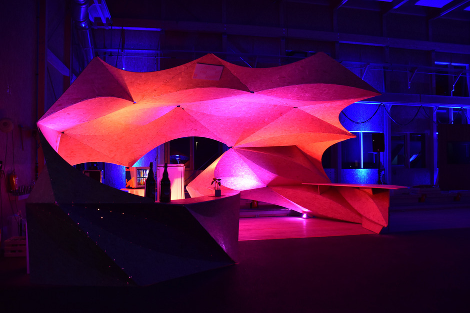 Eine Bar aus gebogenen Holzplatten: Das bei Holzbau Saurer gefertigte Holzfaltungsprojekt der Uni Innsbruck wurde bei der Feier präsentiert.