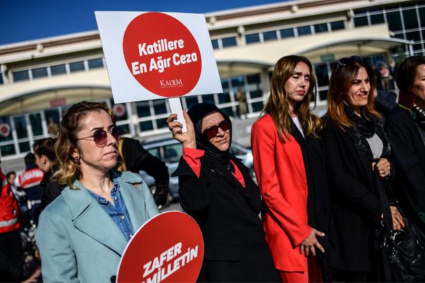 """Frauen vor dem Gericht fordern mit Schildern die """"härteste Strafe für die Mörder""""."""