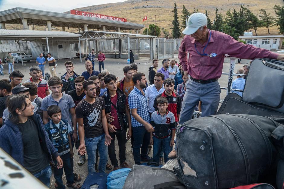 Syrer packen ihr Hab und Gut auf einen Laster an der türkischen Grenze.