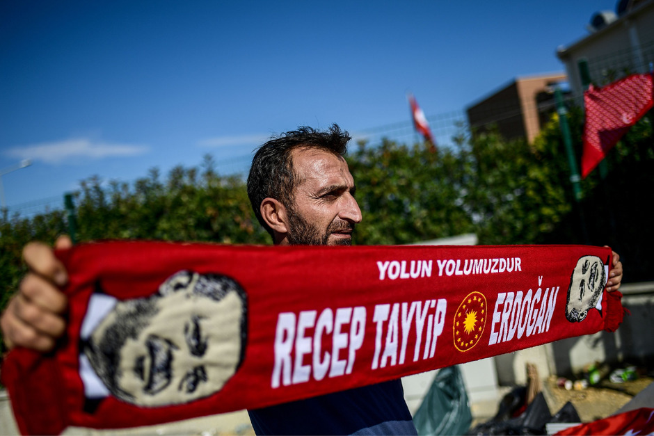 Ein Verkäufer bietet vor einem Gerichtsgebäude in der Türkei Erdogan-Schals an.