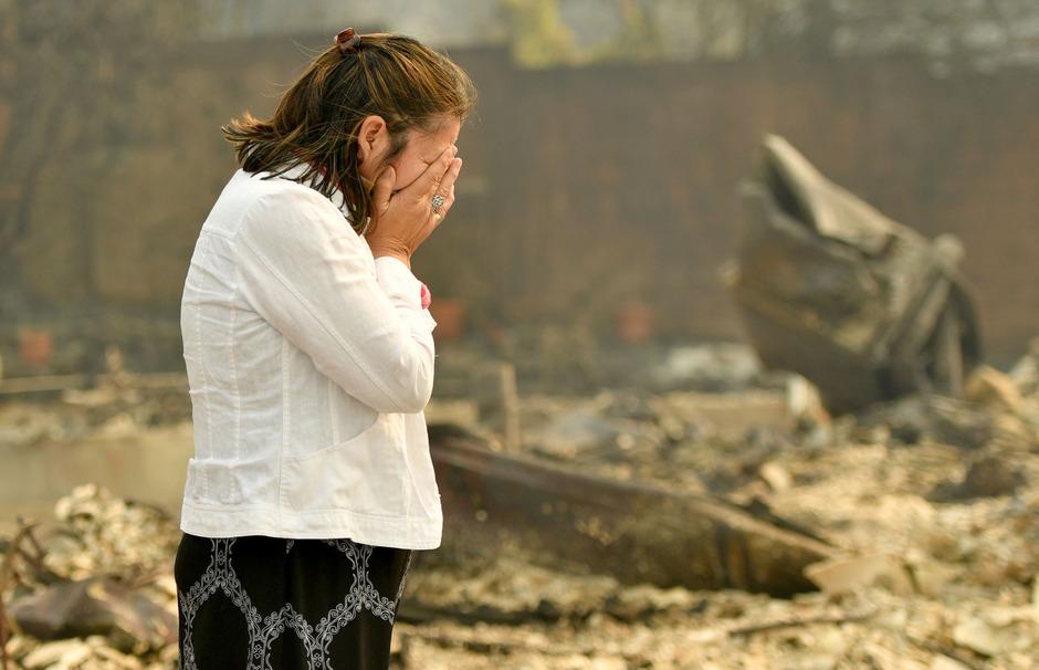 Eine Frau steht fassunglos vor den Trümmern ihrer Existenz.