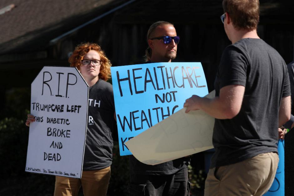 """Eine Demonstrantin hält ein Schild in die Höhe mit der Aufschrift """"Ruhe in Frieden. Trumpcare hat diesen Diabetiker pleite und tot zurückgelassen""""."""