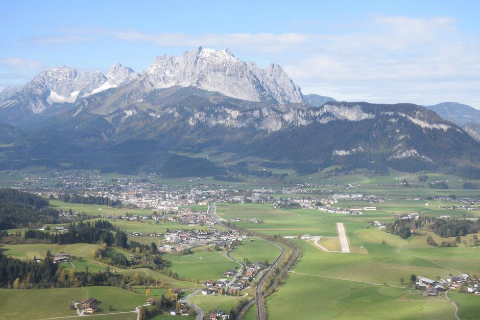 Ein Blick auf St.Johann aus der Luft: der Wilde Kaiser im Hintergrund, davor die Gemeinde und rechts die Start- und Landebahn des Flugplatzes.