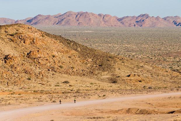 Wie Sandkörner schauen die zwei Radfahrer in der Weite der Wüste aus.