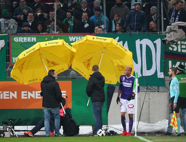 Mit Sonnenschirmen mussten die Austria-Kicker bei Eckbällen im Derby vor Gegenständen aus dem Rapid-Sektor geschützt werden.