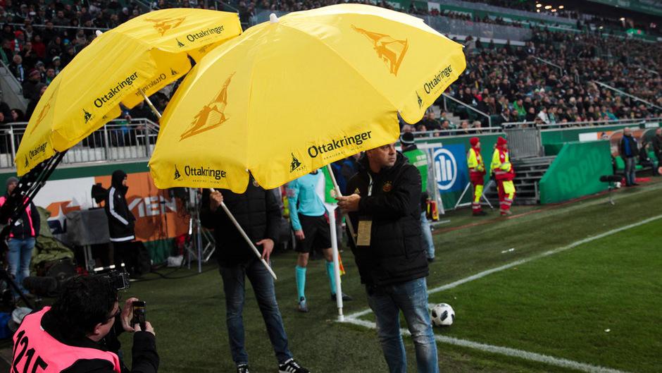 Ordner mussten beim Wiener Derby mit Schirmen die Spieler bei der Eckfahne vor Wurfgegenständen schützen.