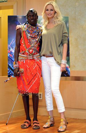 Das Model Adriana Karembeu posiert 2011 bei der Vorstellung einer Modelinie mit einem Massai.