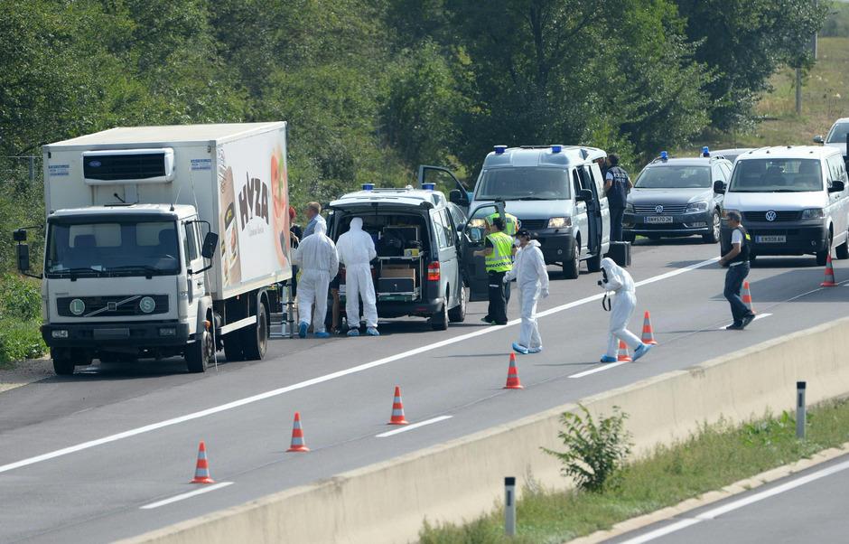 Einsatzkräfte der Polizei und der Spurensicherung neben dem abgestellten Lkw, in dem die toten Flüchtlinge gefunden wurden.