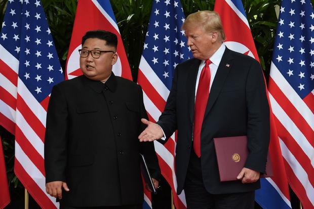 US-Präsident Donald Trump und Nordkoreas Staatschef Kim Jong-un inszenierten ihre erste Begegnung vor Flaggen der beiden Länder.