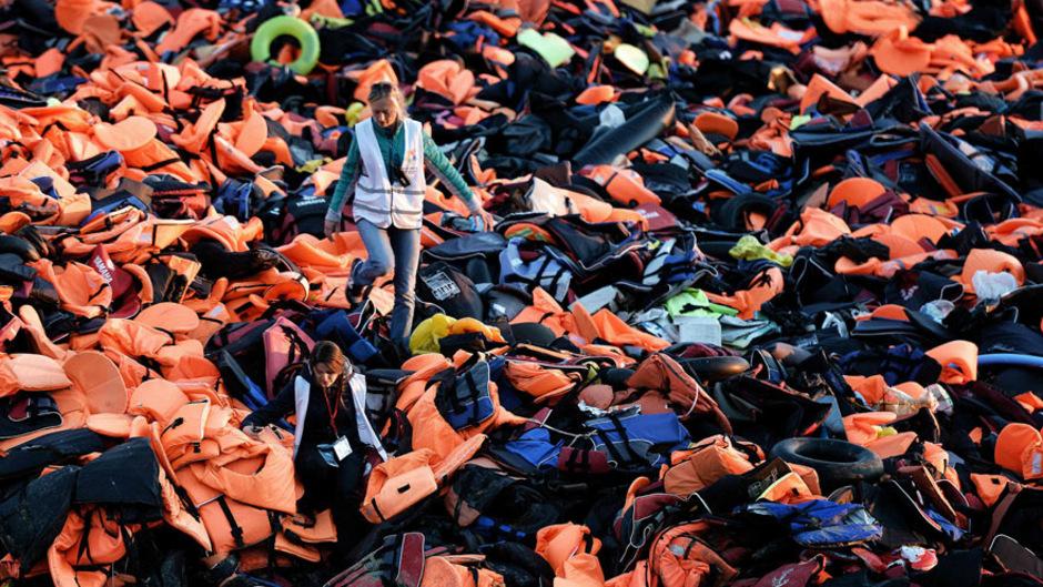 Freiwillige Helfer auf der griechischen Insel Lesbos bahnen sich den Weg durch Hunderte von Flüchtlingen zurückgelassene Schwimmwesten.