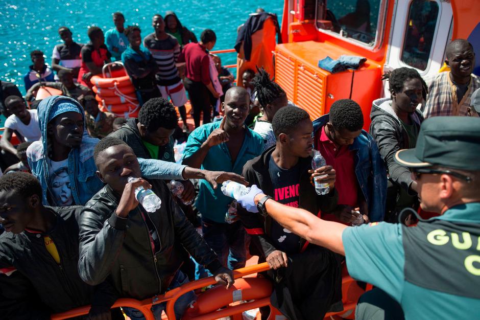 Mitarbeiter der spanischen Zivilschutzbehörde verteilen Wasserflaschen an ankommende Flüchtlinge im Ort Tarifa ganz im Süden Spaniens.