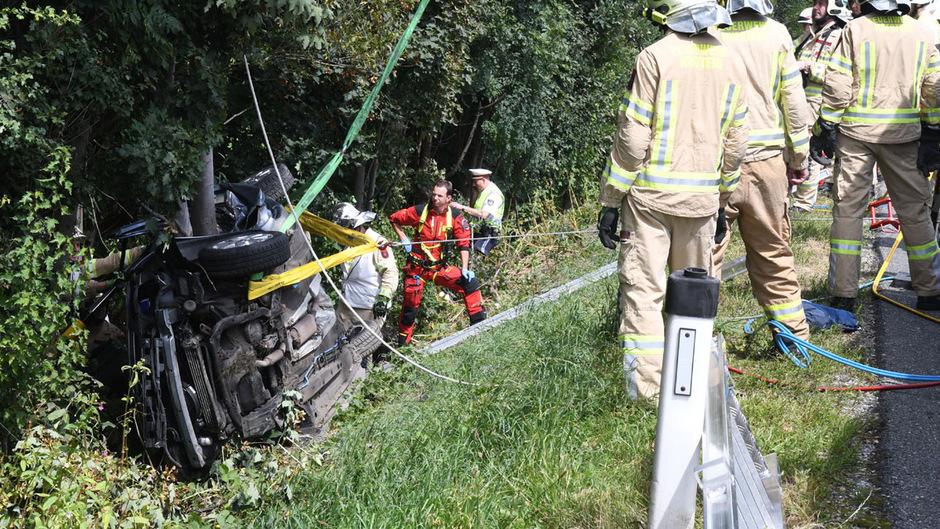 Rettungsmannschaften bergen das Wrack aus einem Graben.