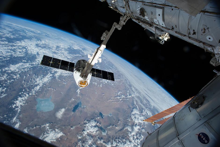 Ein Greifarm der ISS fährt aus und holt ein SpaceX-Dragon-Modul heran.