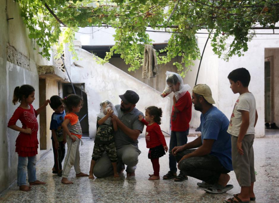Männer zeigen Kindern in Idlib, wie man improvisierte Gasmaken verwendet. Die Angst vor einem Angriff der syrischen Armee mit GIftgas wächst.