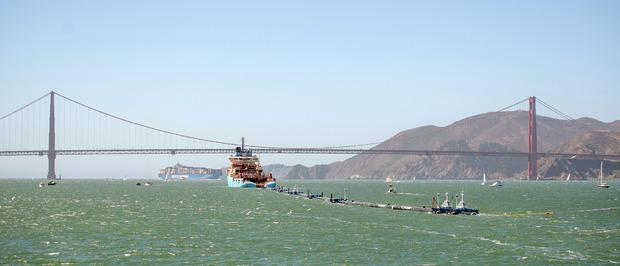 """Eine riesige schwarze Kunststoffröhre mit der Aufschrift """"System 001"""" zieht durch die Bucht von San Francisco. Im Schlepptau eines Schiffes hält sie Kurs auf den größten Müllteppich der Welt."""