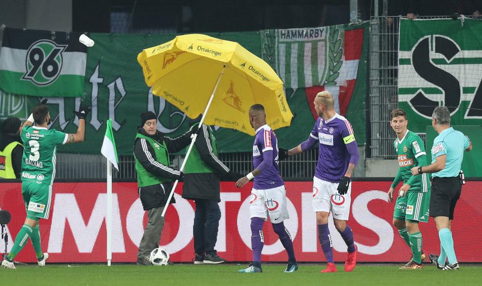 Szenen, die der Fußball nicht braucht: Mit Sonnenschirmen mussten die Austria-Spieler vor den Wurfgegenständen aus dem Rapid-Sektor geschützt werden.