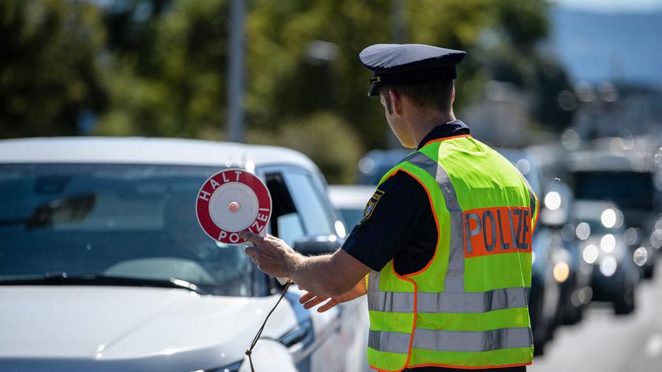 Ein Polizist der bayerischen Polizei winkt an der Grenzkontrollstelle in Freilassing ein von Salzburg nach Deutschland kommendes Fahrzeug in die Kontrollstelle.