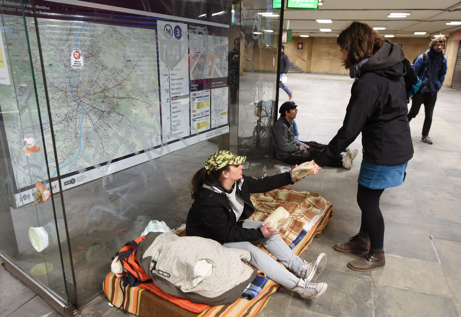 Eine Helferin teilt Nahrung an Obdachlose aus.