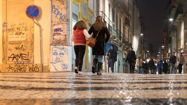 Passanten gehen über im Regen glitzerndes Pflaster an der Praca de Carlos Alberto.